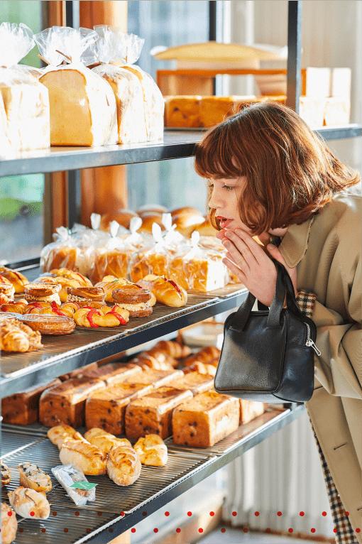 たくさんのパンを美味しそうに見つめる女性の姿